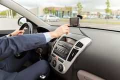 Close up of man with gps navigator driving car. Transport, business trip, technology, navigation and people concept - close up of male hand using gps navigator stock image