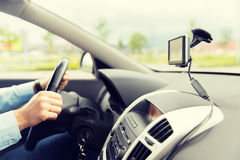 Close up of man with gps navigator driving car. Transport, trip, technology, navigation and people concept - close up of male hand using gps navigator while stock photos
