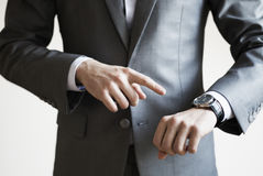 Close up of a man in grey suit pointing at watch on his hand wit. H white background Royalty Free Stock Photo