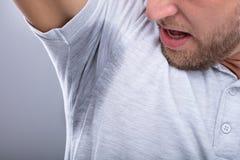 Man Looking At His Sweaty Armpit. Close-up Of A Man In Grey T-shirt Looking At His Sweaty Armpit stock photos