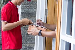 Delivery man delivering box. Close up man hand appending receive sign signature after accepting a delivery of boxes Stock Photography