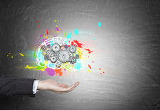 Close up of man hand with brain, gears, blackboard. Close up of man hand in a black suit holding a hovering colorful brain and gears sketch drawn on a blackboard Royalty Free Stock Images