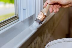 Close up of man hand carefully painting the edge of an house window royalty free stock image