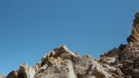 Close up of man hand climbing to the top of mountain.