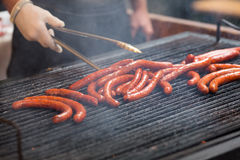 Close-up of man hand, cooking spicy browned sausages on the hot flat grill . Street food and barbecue concept Stock Photography