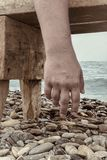 Close up man hand hanging from a beach bench, pebbles and sea on background. Atmosphere of total exhausting, prostrate, solitude,. Loneliness. Outdoors, copy royalty free stock images
