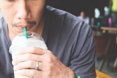 Close up of man hand holding a cup of iced coffee. In coffee shop Royalty Free Stock Photography