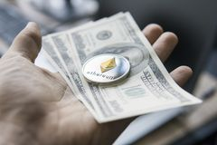 Close up man hand holding Ethereum coin with a us dollar bill against a laptop on the back. Ethereum is a crypto. Currency and a worldwide payment system Stock Images