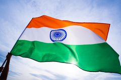 Close up man hand holding India flag on the blue sky Royalty Free Stock Images