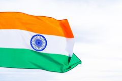 Close up man hand holding India flag on the blue sky background. Stock Photo