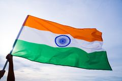 Close up man hand holding India flag on the blue sky Royalty Free Stock Image