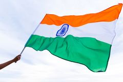 Close up man hand holding India flag on the blue sky Royalty Free Stock Photo