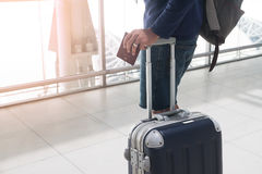 Close up of man hand holding passport and luggage suitcase. At airport stock photo