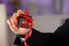 Close up of man hand holding small gift with ribbon. royalty free stock photos