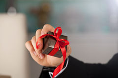 Close up of man hand holding small gift with ribbon. royalty free stock photo