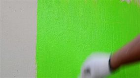 Close up man hand painting green color on the wall stock footage