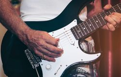 Close up of man hand playing guitar on stage for background. royalty free stock image