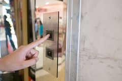 Close up man hand press a up button of elevator inside the building for upper high level floor stock images
