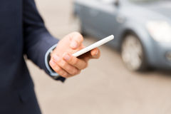Close up of man hand with smartphone and car Stock Photos