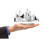 Close up of man hand with smartphone city sketch. Business and architecture concept - close up of man hand with smartphone and city sketch royalty free stock image