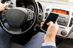 Close up of man hand with smartphone driving car Stock Photography