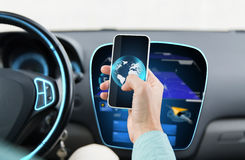 Close up of man hand with smartphone driving car Royalty Free Stock Image