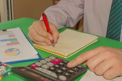 Close up Man hand using calculator and writing make note with calculate about cost at home office. Business concept. The Man are. Using a calculator on the royalty free stock images