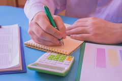 Close up Man hand using calculator and writing make note with calculate about cost at home office. Business concept. The Man are. Using a calculator on the royalty free stock photo