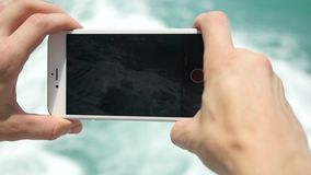 Close up of man hand using smart phone on the sea waves water blue background. slow motion. 1920x1080