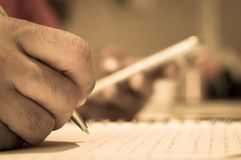 Close up of a man hand writing on his notebook while holding a mobile smart phone Royalty Free Stock Photo