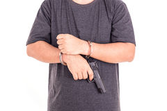 Close up man with handcuffs and gun on hands isolated on white Stock Images