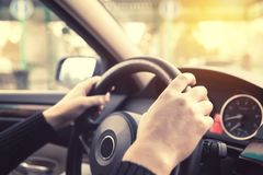 Close up of man hands driving a car during sunlight. Vintage fil Stock Photos