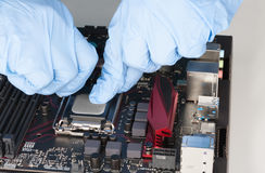 Close up of man hands with gloves openning slot for CPU on  moth Royalty Free Stock Photo