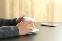 Man hands holding a coffee cup on a table. Close up of a man hands holding a coffee cup on a table stock photo