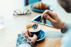 Close up of man hands holding cup of coffee. Croissant is on background. stock photo