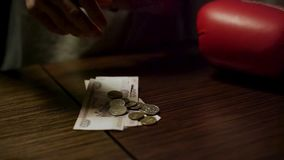 Close up of man hands holding an open leather wallet with a few coins inside over a old wooden table with paper money stock video footage