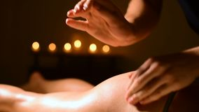 Close-up of a man. Hands of a massage therapist in a spa do massage with light blows to a young woman. The concept of. Care and beauty. Buttocks cellulite stock video footage