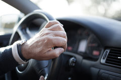 Close up of man hands moving steering wheel, driving a car. Stock Photo