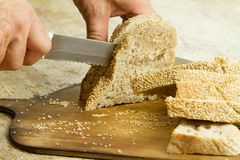 Close up of man hands slicing a loaf of homemade bread with sesame seeds on a wooden cutting board in selective focus on wooden royalty free stock images