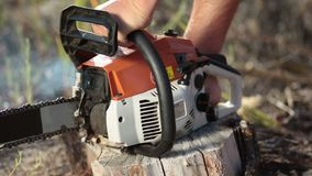 Close up man hands starting chainsaw Stock Photo