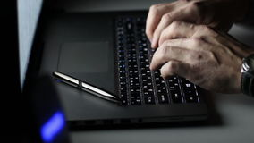 Close-up of a man hands typing on a laptop keyboard in the durck. The notebook is a pen stock video footage