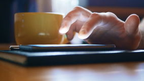 Close up of man hands using smartphone for messaging. The phone rests on a notebook and is next to a cup of coffee stock video