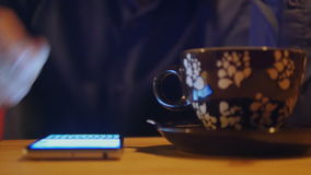 Close up of man hands using smartphone for messaging. The phone rests on a table and is next to a cup of coffee. Man. Drinks coffee and chatting stock footage