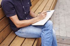 Close-up of man hands writing in note book outside in public space. Concept of education or business. Close-up of man hands writing in note book outside in Stock Photo
