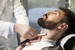 Close up of a man having his hair cut stock image
