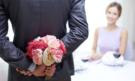 Close up of man hiding flowers behind from woman. Restaurant, people, celebration and holiday concept - close up of men hiding flowers behind from women at Royalty Free Stock Photos