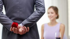 Close up of man hiding red box behind from woman. Couple, love, proposal and holiday concept - close up of men hiding red box behind from women at restaurant Royalty Free Stock Photos