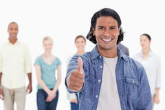 Close-up of a man with his thumb-up with people behind Stock Photo