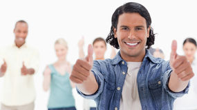 Close-up of a man with his thumbs-up with people behind. Close-up of a men with his thumbs-up with people behind against white background Royalty Free Stock Photography