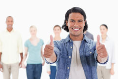 Close-up of a man with his thumbs-up with people behind Stock Photo